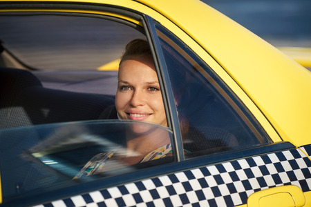 blond woman in yellow taxi looking out of car window and smiling. Tourism and business travel
