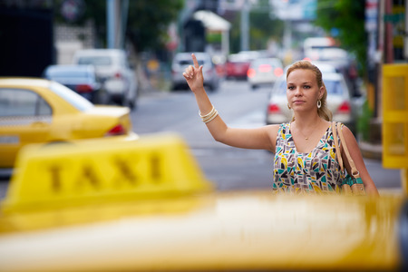 stopping: blond businesswoman calling yellow taxi with arm raised in street. Tourism and business travel  Stock Photo