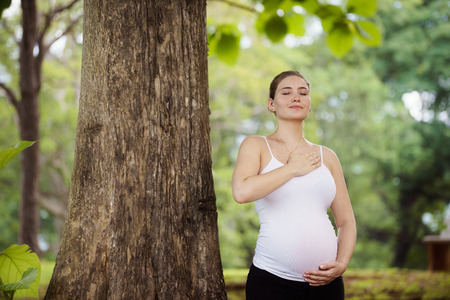 Portrait of white beautiful pregnant woman doing yoga exercise in park near tree, touching belly and heart