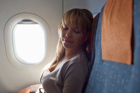 People and travel, young woman traveling on airplane and sleeping. Copy space on flight seat Stock Photo