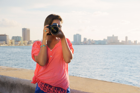 habana: Portrait of young girl in la habana, cuba, taking pictures and photo looking at camera through viewfinder