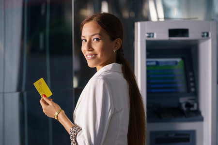 Portrait of latina businesswoman withdrawing dollar from atm cash machine and showing credit card to camera  Banque d'images