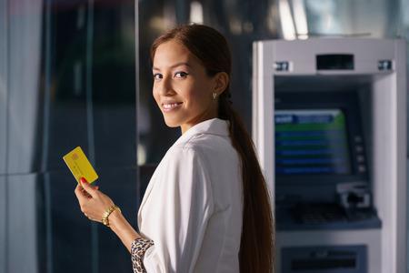 Retrato de la empresaria latina retirar dólares del cajero automático y muestra la tarjeta de crédito a la cámara Foto de archivo