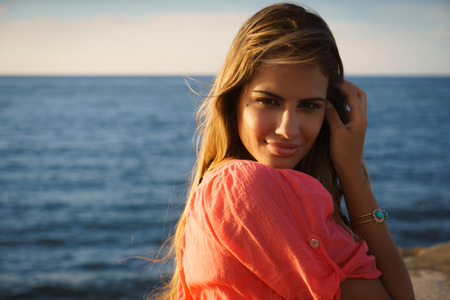 Portrait of beautiful young latina woman on holidays, sitting near sea and smiling at camera