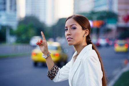 ラテン アメリカ ビジネスの女性が通りに立っている、仕事の後の黄色のタクシーを呼び出す