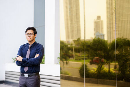 Portrait of chinese businessman standing with arms crossed near office building in Panama. Reflections of city on mirror photo
