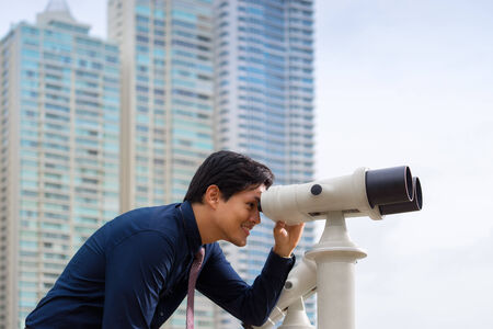Portrait of young chinese business man standing in Panama City and looking through binoculars. Concept of forecasting, career, success photo