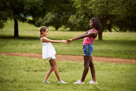 niños jugando en el parque: Dos niñas hispanas y africanas jugando anillo alrededor del rosie en el parque público y tomados de la mano Foto de archivo