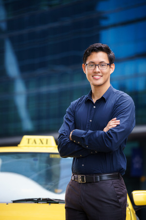 Portrait of happy chinese taxi driver leaning on yellow car with arms crossed, smiling and looking at camera Foto de archivo