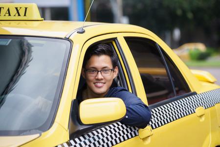 Retrato de taxista chino feliz en el coche amarillo sonriente y mirando a cámara Foto de archivo