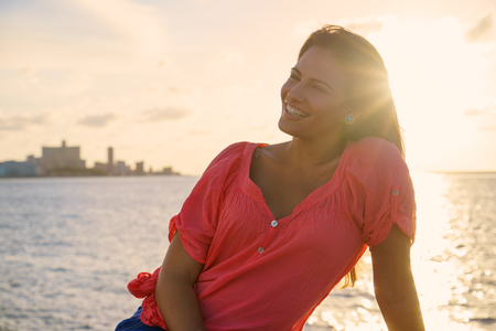 Portrait of beautiful young latina woman on holidays in Cuba, Havana, sitting near sea and smiling looking away photo