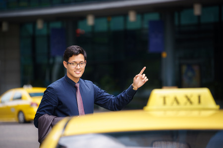 tourists stop: Asian business man standing near office buildings, calling yellow taxi and entering in car