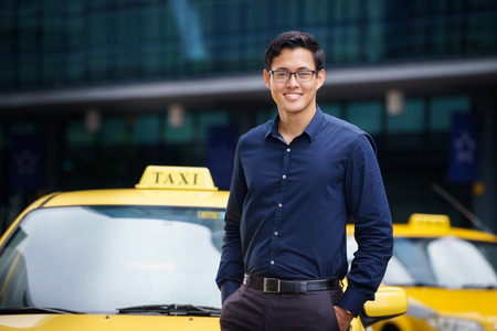 yellow taxi: Portrait of happy chinese taxi driver leaning on yellow car with arms crossed, smiling and looking at camera Stock Photo