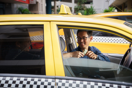 tours: Asian man working as taxi driver in yellow car, with female client paying cash and leaving
