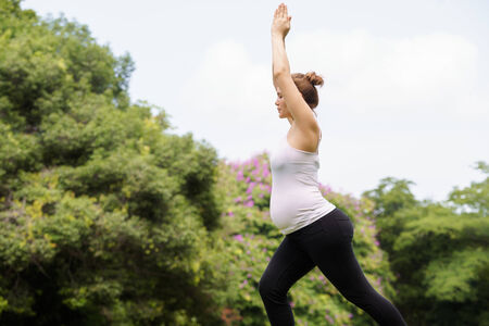 expectant arms: Portrait of white beautiful pregnant woman doing yoga exercise in park, with arms raised Stock Photo