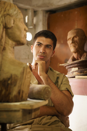 art thinking: Portrait of happy young student in art class, learning crafts profession, looking at wooden statue and smiling. Success, career and confidence