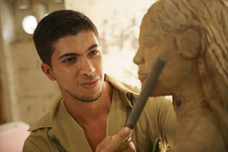 L'uomo, la gente, lavoro, giovane studente al lavoro di apprendimento professione artigiano in classe arte, lavorando con la statua in legno e intaglio del legno