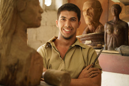 sculptor: Portrait of man working, young student in art class, learning crafts profession, working with wooden statue and looking at camera