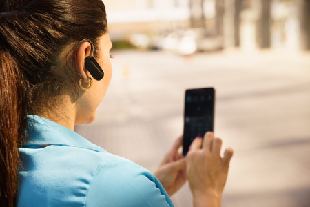 headset woman: Mid adult hispanic person with mobile phone and bluetooth headset, typing on telephone in the street Stock Photo