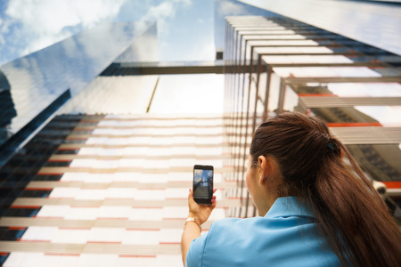 low  angle: Rear view of corporate woman taking still picture of skyscraper and office building with mobile phone. Low angle