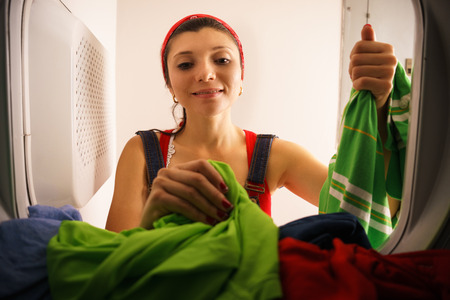 Young hispanic woman at home, doing chores and housekeeping, collecting clothes and dresses from laundry tumble dryer, drying machine Stock Photo