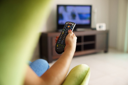 tv remote: Over the shoulder view of girl sitting on sofa holding tv remote and surfing programs on television Stock Photo