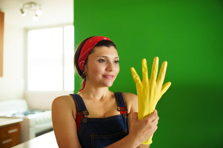 latex woman: Young hispanic woman at home, doing chores and housekeeping work in kitchen, girl putting on yellow latex gloves