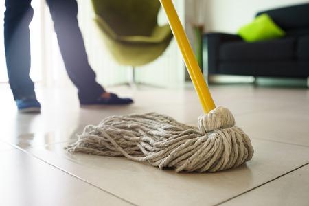 Mujer en casa, haciendo las tareas domésticas y de limpieza, limpiando el suelo con agua en la sala de estar. Centrarse en el suelo y la fregona Foto de archivo