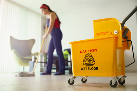 mop floor: Young hispanic woman at home, doing chores and housekeeping, wiping floor with water in living room