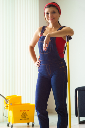doing chores: Happy young hispanic woman at home, doing chores and housekeeping, wiping floor with water, looking at camera and smiling. Daily job of wife, housewife working