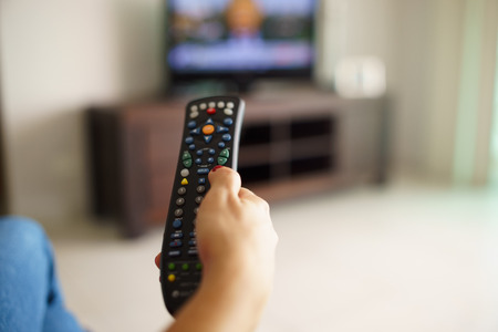 channel surfing: Over the shoulder view of girl sitting on sofa holding tv remote and surfing programs on television Stock Photo