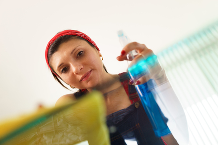 domestic chore: Young hispanic woman at home, doing chores and housekeeping, wiping glass table in living room