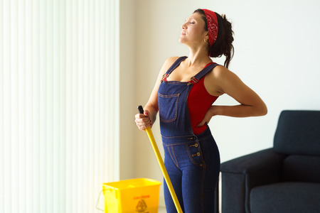 mopping: Happy young hispanic woman at home, doing chores and housekeeping, suffering pain in the back Stock Photo