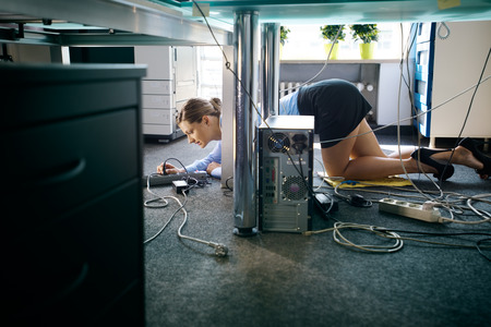 Female assistant working in office, plugging cables to computer and electronic equipment, messing around with wires. Copy space photo