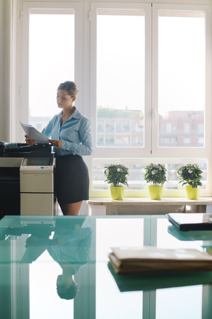 Female secretary working in office, copying document and paperwork with copy machine in modern office photo