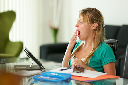 Young blond woman bored while studying, laying on desk and yawning