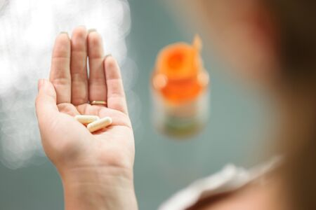 pills bottle: Close up view of young woman holding ginseng vitamins and minerals pills in hand with capsule bottle on table. High angle view Stock Photo