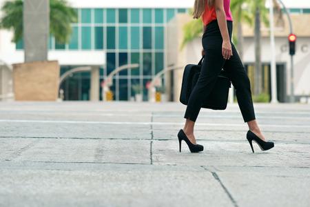 vrouwen: Weergave van zakelijke vrouw lopen in de stad straat met laptop tas, woon-werkverkeer en naar het werk gaan in de ochtend. Exemplaar ruimte, taille naar beneden
