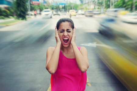 Portrait of woman standing still in the middle of a street with cars passing by fast, screaming stressed and frustrated Stockfoto