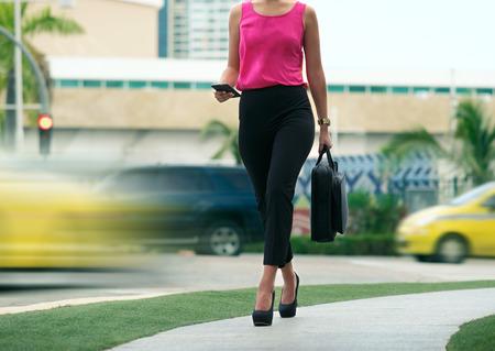 Recorta la vista de la mujer de negocios que recorre en calle de la ciudad con bolsa de portátil, hablando por teléfono móvil e ir a trabajar en la mañana
