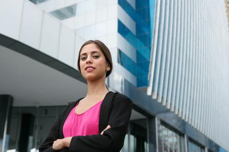 Retrato de joven confía en la persona de negocios hispana con los brazos cruzados, mirando a la cámara y sonriendo