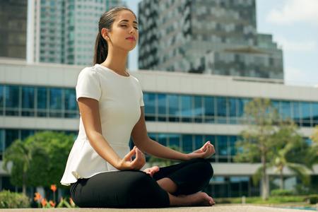 Young destacó mujer de negocios hispano haciendo yoga fuera del edificio de la oficina, sentado en posición de loto con las manos en las rodillas en la calle. Concepto de largas horas de trabajo y la necesidad de vacaciones sin estrés