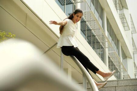 bajando escaleras: Empresaria hispánica feliz, niña, mujer latina, gerente Fermale éxito deslizamiento sobre riel. Alegría, felicidad para el éxito del negocio y de la carrera