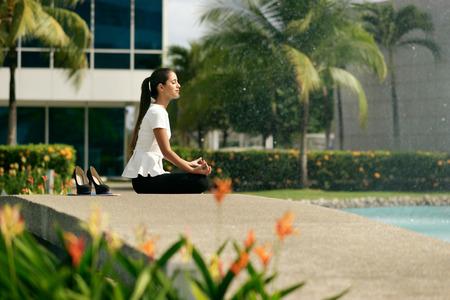 papeles oficina: Young destacó mujer de negocios hispano haciendo yoga fuera del edificio de la oficina, sentado en posición de loto con las manos en las rodillas en la calle. Concepto de largas horas de trabajo y la necesidad de vacaciones sin estrés