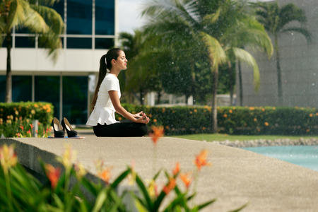 office break: Young stressed hispanic business woman doing yoga outside office building, sitting in lotus position with hands on knees in the street. Concept of long working hours and need of stress free break
