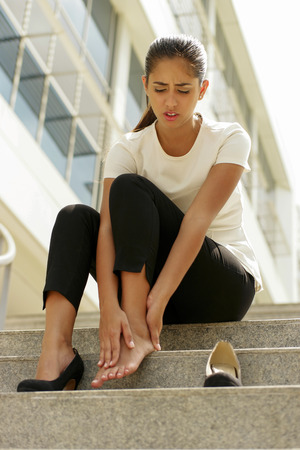 exhausted worker: Portrait of latina woman walking on high heels and feeling pain, massaging feet with hand and sitting on stairs Stock Photo