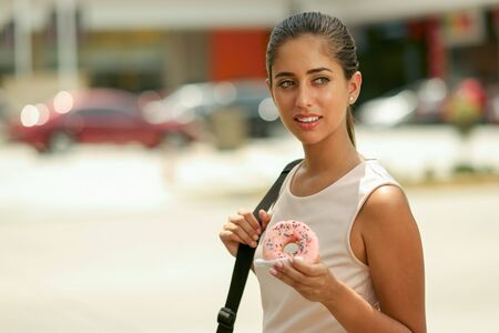 Young business woman walking to job doing breakfast eating pink donut from fast food on street. Front view, copy space