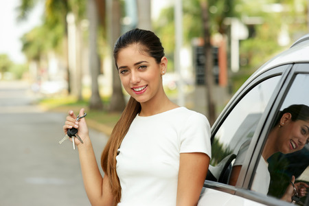hand key: Young adult hispanic woman holding keys of new white car, leaning on auto door. She smiles and looks proud at camera, showing the keys. Waist up portrait