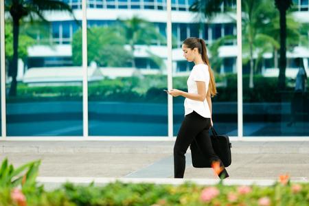 Weergave van zakelijke vrouw lopen in de stad straat met laptop tas, chatten op de mobiele telefoon en gaat werken in de ochtend