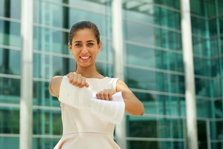 contrato de trabajo: Retrato de hermosa empresaria latina dimite de trabajo, arrancando un contrato de trabajo y que parece feliz en la c�mara, sonriendo y sosteniendo el documento. La dama est� de pie delante de un moderno edificio de oficinas.
